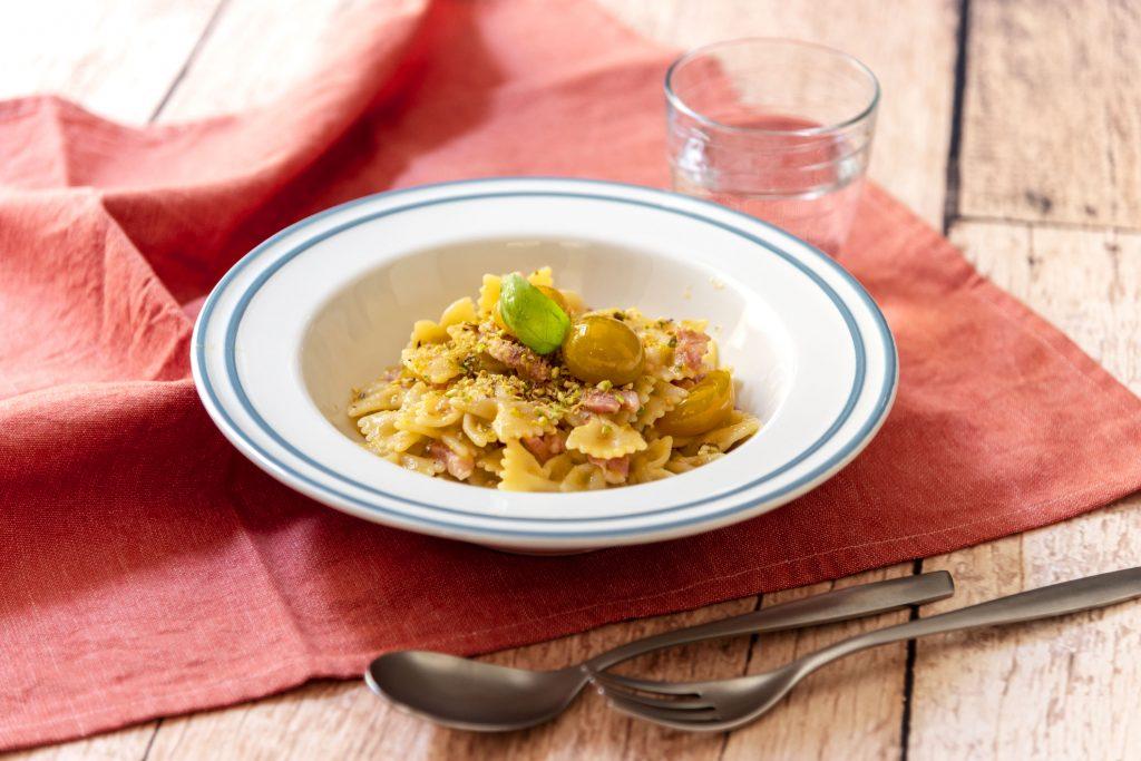 Farfalle con pomodorino giallo, pancetta e pistacchio
